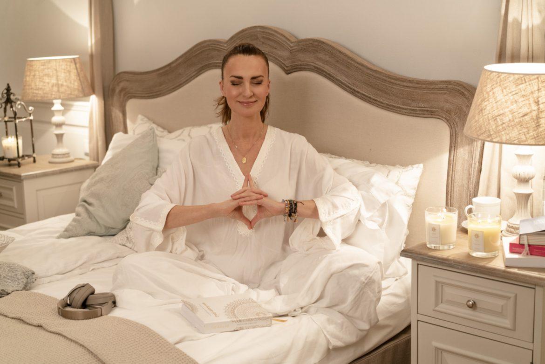 Medytacja dla początkujących - Agnieszka Maciąg medytuje w swojej sypialni w blasku świec.