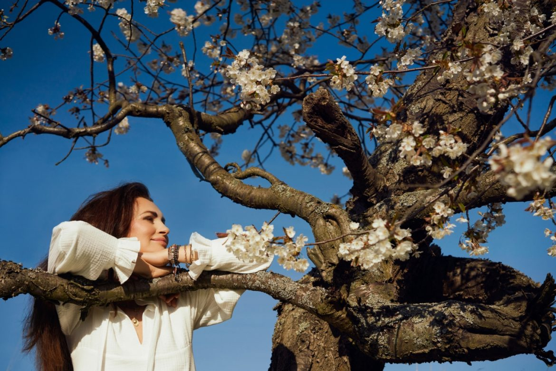 Afirmacje Agnieszki Maciąg - pozytywne myśli i słowa to piękne życie. Agnieszka Maciąg opiera się rękami o gałąź drzewa z wiosennymi kwiatami.