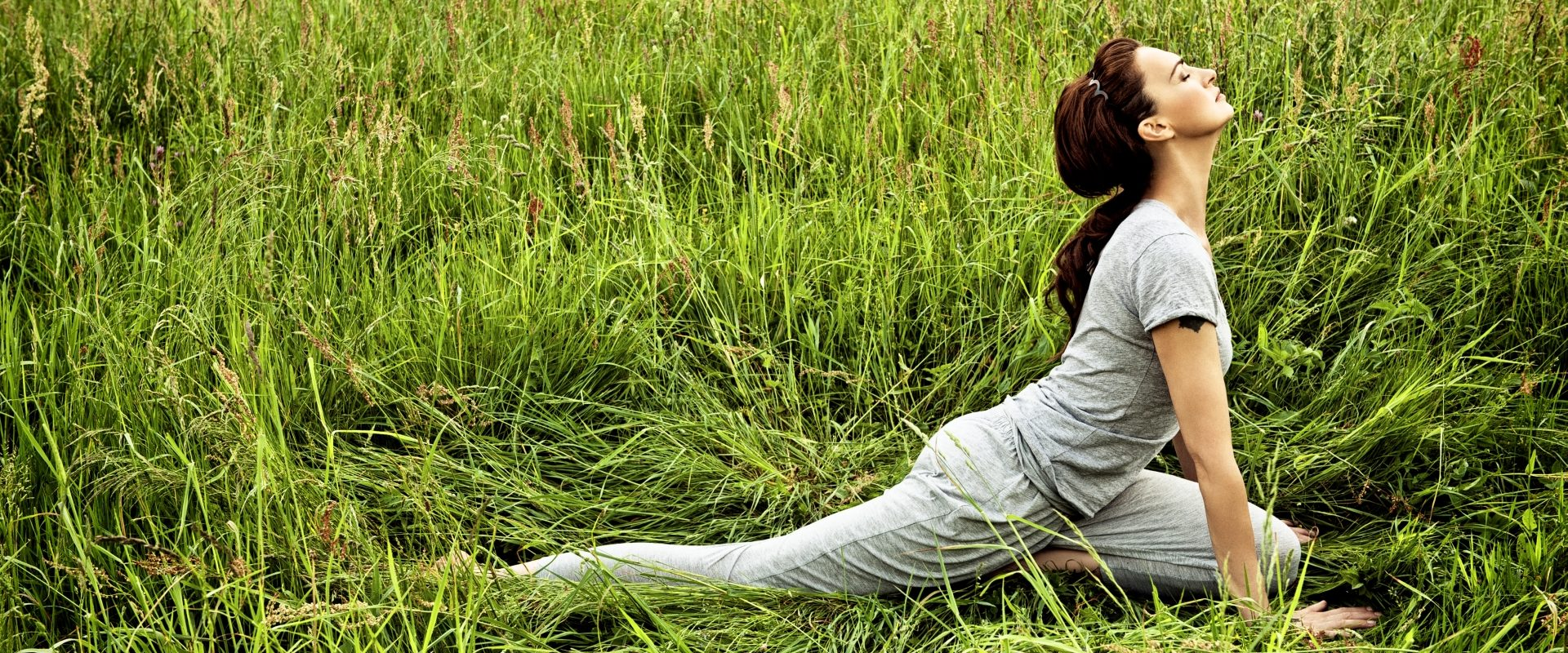 Agnieszka Maciąg ćwiczy jogę i medytuje na trawie.