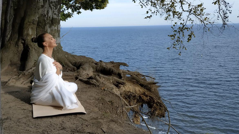 Mantry - pieśni, które dają siłę i uzdrawiają. Agnieszka Maciąg medytuje na skarpie nad brzegiem morza.