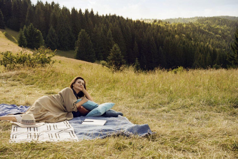 Agnieszka Maciąg leży na kocu na górskiej polanie. Opowiada o ciałopozytywności i o tym, jak nauczyć się kochać swoje ciało takim, jakie jest.