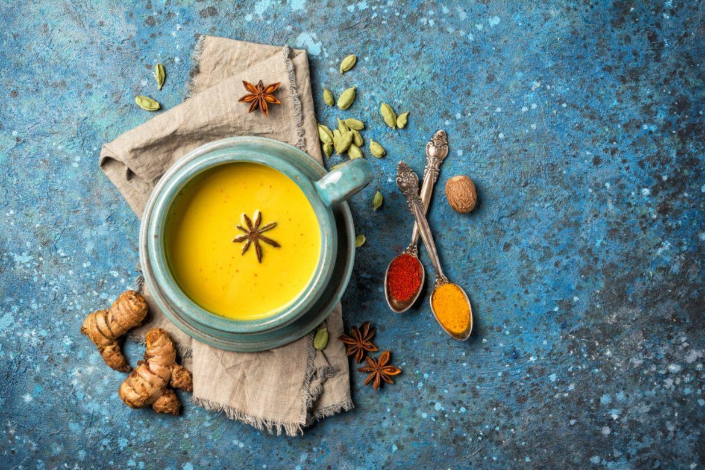 Jak zbudować odporność według ajurwedy? Miseczka napoju z kurkumy i goździków (złotego mleka) na niebieskim blacie, wokół leżą przyprawy, będące składnikami napoju.