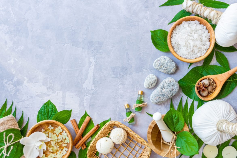 Ajurweda a Hashimoto - na czym polega leczenie ajurwedyjskie choroby autoimmunologicznej tarczycy? Widok z góry na przybory do masażu ajurwedyjskiego leżące na szarym blacie.