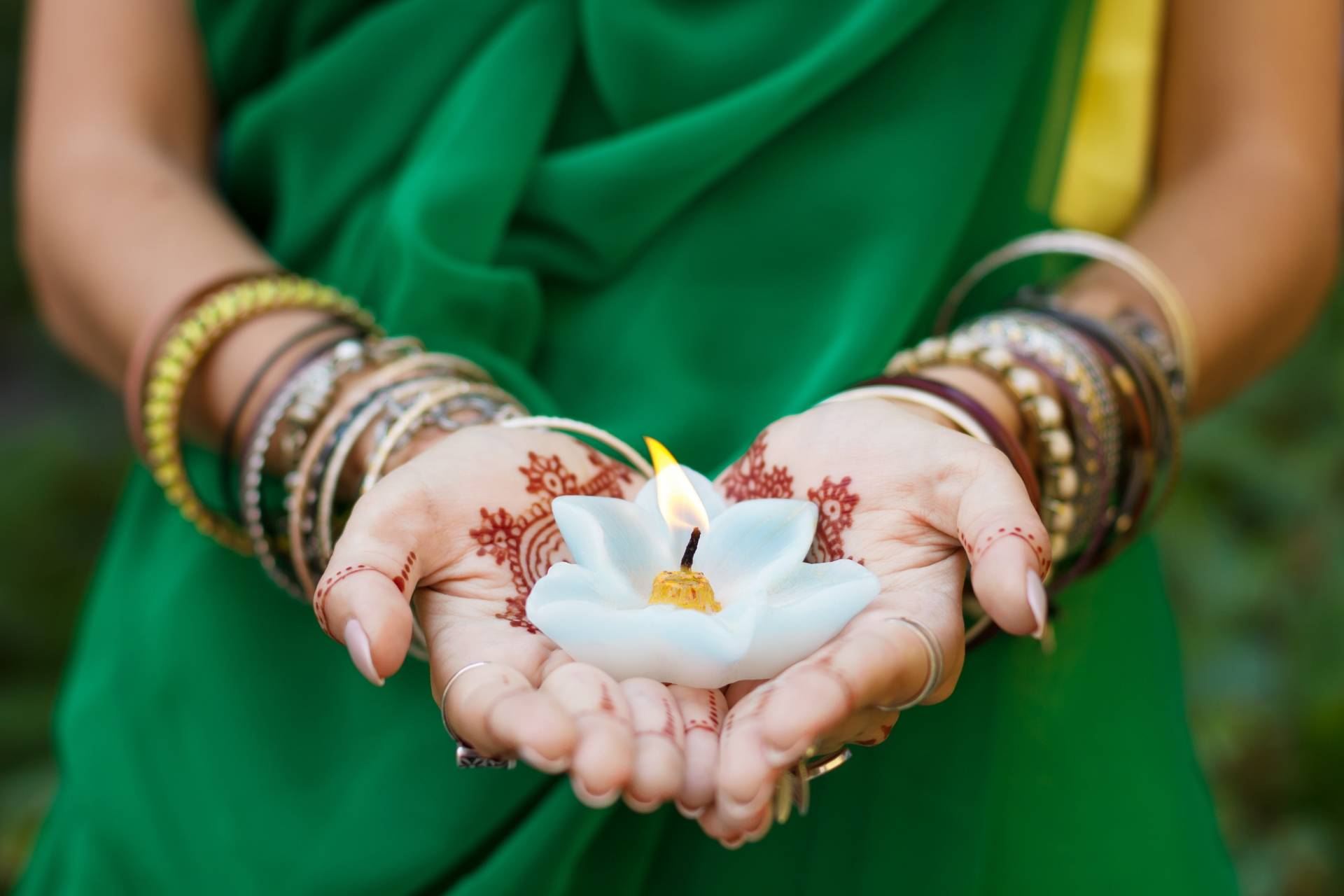 Ajurweda - najstarszy system medyczny na świecie. Kobieta ubrana w tradycyjny strój trzyma zapaloną świecę w kształcie kwiatka.