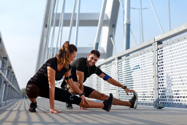 Sport jest dla wszystkich - jakie są korzyści ze sportu amatorskiego, a jakie zagrożenia niesie sport wyczynowy? Kobieta i mężczyzna rozciągają się po treningu w mieście.
