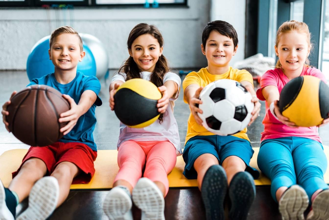 Jak walczyć z otyłością u dzieci? Jakie są jej przyczyny i skutki? Szczupłe dzieci pozują do zdjęcia z piłkami, siedząc na macie do ćwiczeń na lekcji WFu.