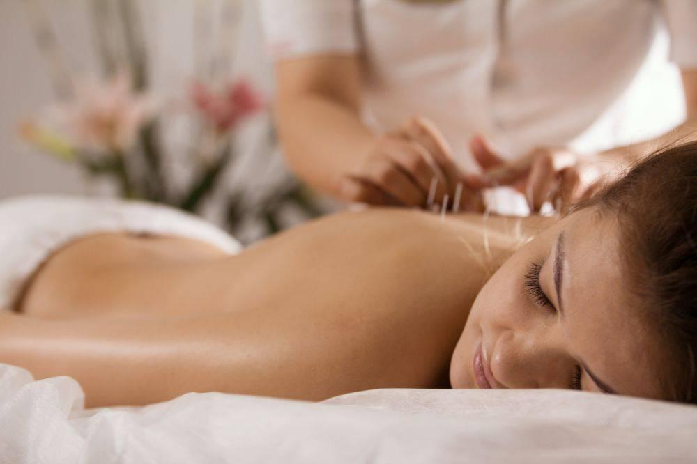 Akupunktura w medycynie chińskiej. Młoda kobieta poddaje się zabiegowi nakłuwania punktów akupunkturowych w gabinecie medycyny chińskiej.