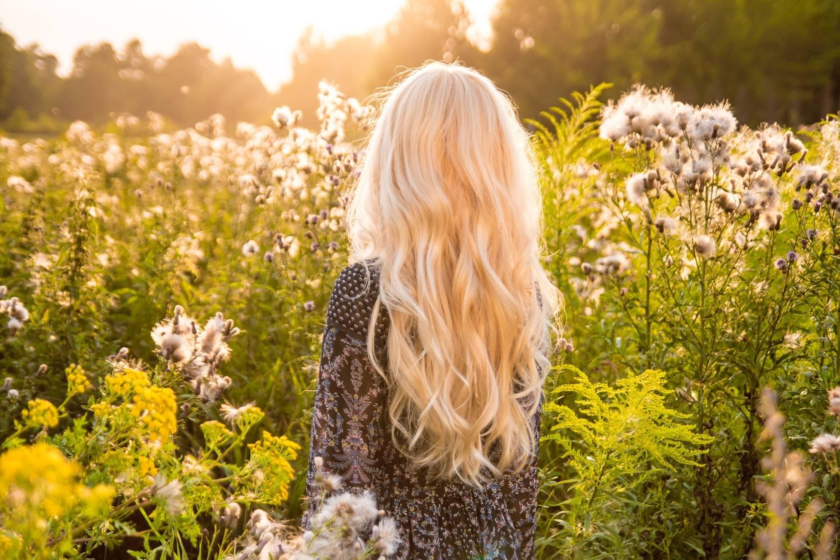 Domowe sposoby na alergię na pyłki. Atrakcyjna, młoda dziewczyna o długich blond włosach stoi na łące, zwrócona tyłem do aparatu.