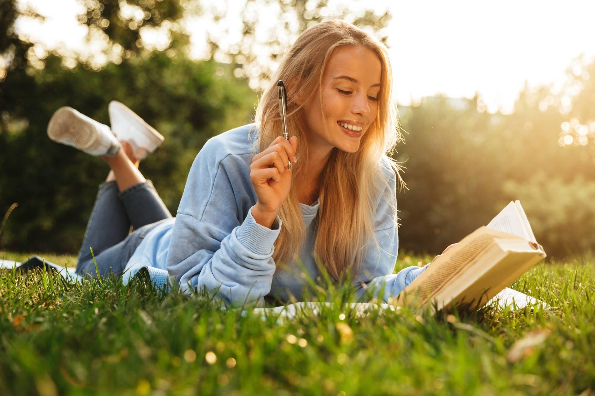 Alergia na pyłki traw i drzew. Młoda uśmiechnięta kobieta w niebieskiej bluzie leży na kocu i czyta książkę.