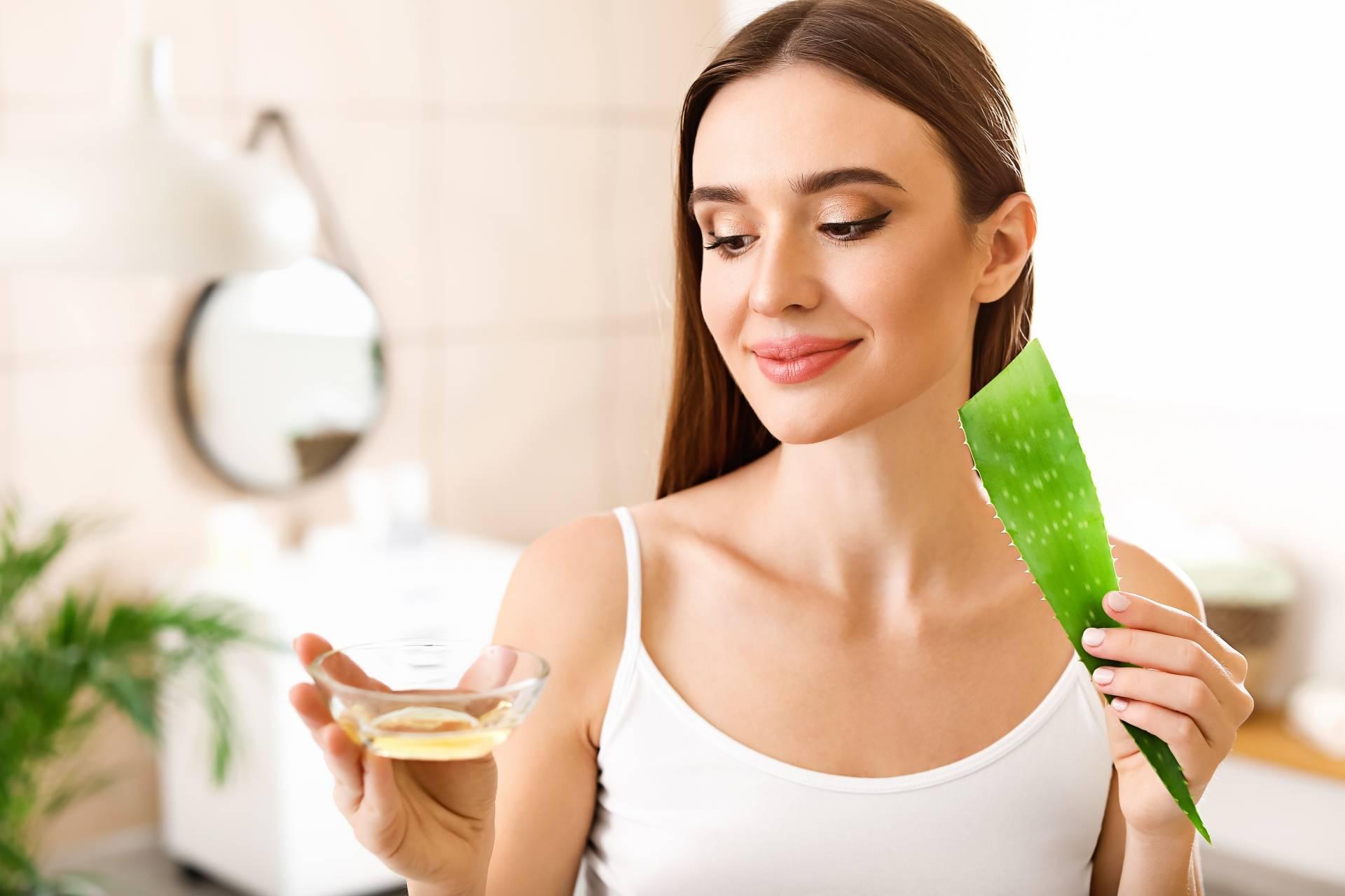 Naturalne kosmetyki do włosów DIY: aloes na włosy. Atrakcyjna kobieta w białym topie stoi w łazience i trzyma w ręku aloes i miseczkę z olejkiem.