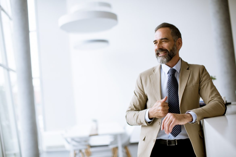 Andropauza - menopauza u mężczyzn - jakie są jej objawy, przyczyny i czy można ją leczyć? Elegancki starszy mężczyzna w garniturze w biurze.
