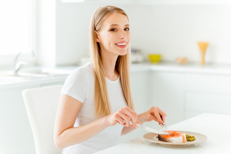 Anemia, czyli niedokrwistość. Jakie są rodzaje niedokrwistości? Jak leczyć anemię, co jeść przy niedokrwistości? Młoda kobieta je posiłek przy stole - rybę bogatą w żelazo.