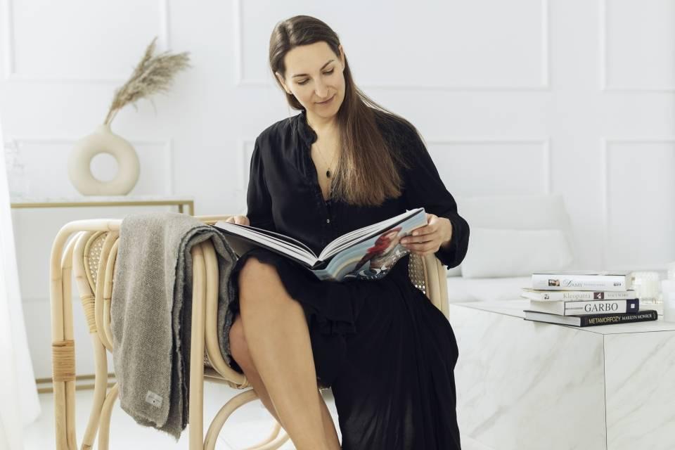 Anna Komierowska-Szweycer w czarnej sukience czyta magazyn modowy.