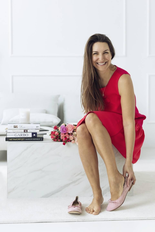 Anna Komierowska-Szweycer w czerwonej sukience siedzi w salonie.