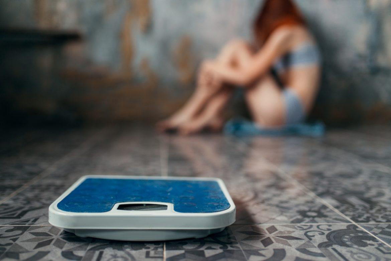 Anoreksja - jakie są jej przyczyny, objawy i jak ją leczyć? Anorektyczka siedzi w kącie, na pierwszym planie widać wagę.