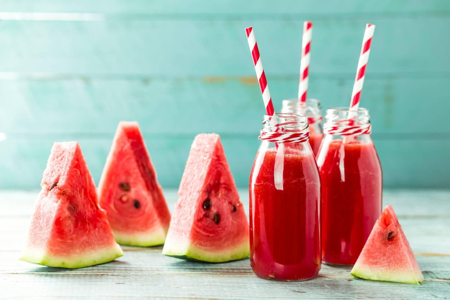 Lemoniada arbuzowa w szklanych butelkach, obok leżą plasterki arbuza. Ile wody dziennie pić latem?
