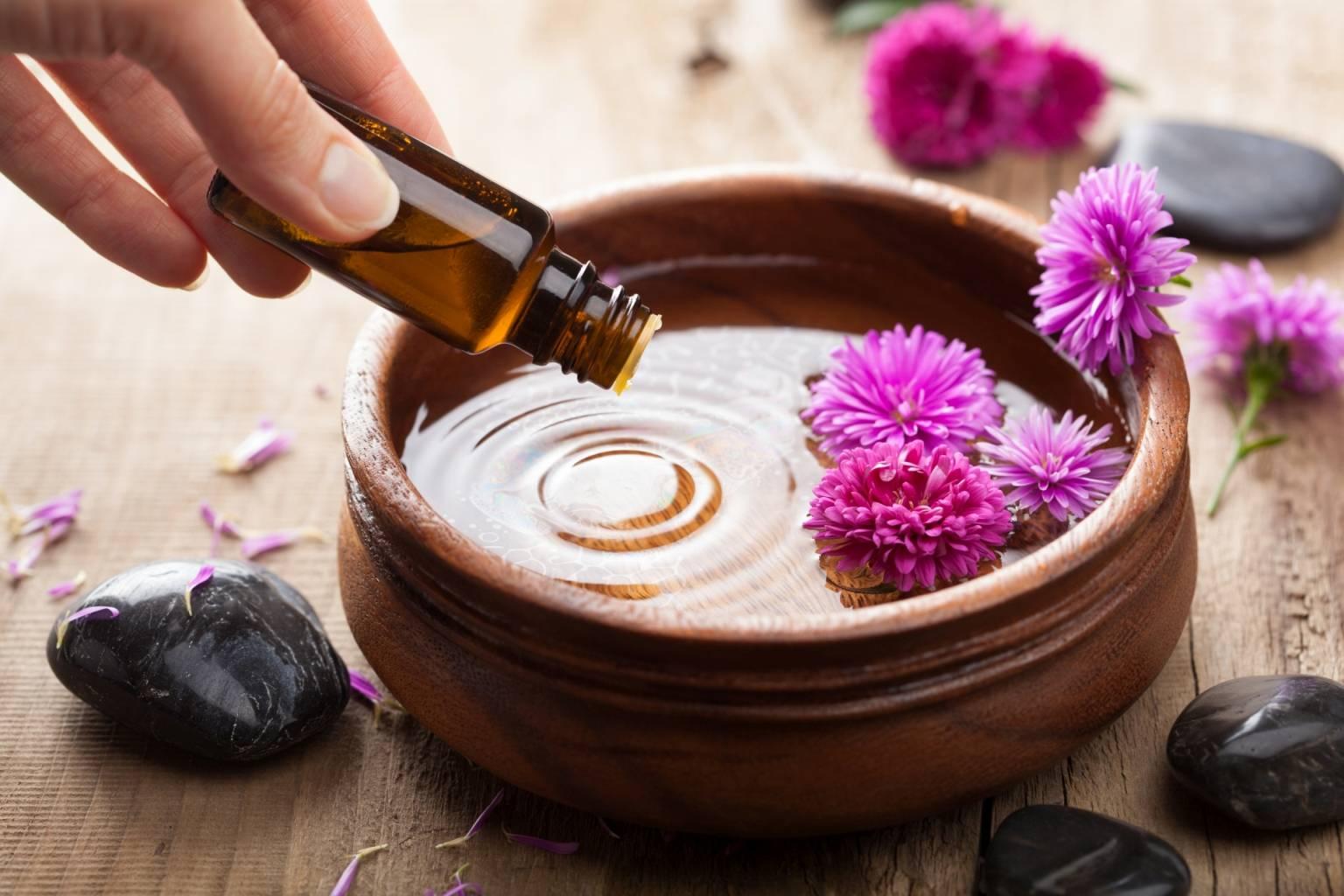 Olejki eteryczne pomagają w leczeniu różnych dolegliwości. Kobieca ręka wkrapla olejek eteryczny do brązowej miski z wodą i różowymi kwiatami polnymi.