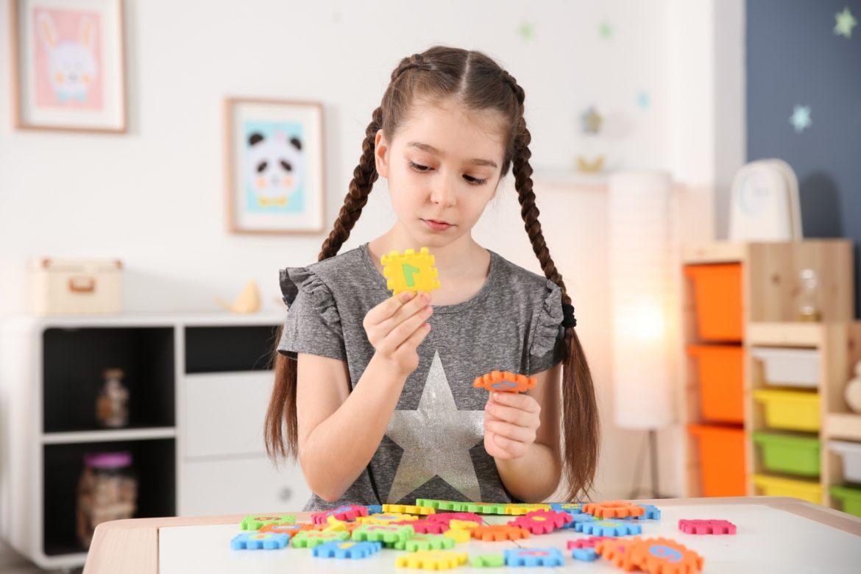Autyzm - objawy, przyczyny, leczenie dziecka z autyzmem. Autystyczna dziewczynka z warkoczykami bawi się w swoim pokoju układanką i przygląda się bacznie jednemu elementowi puzzli.