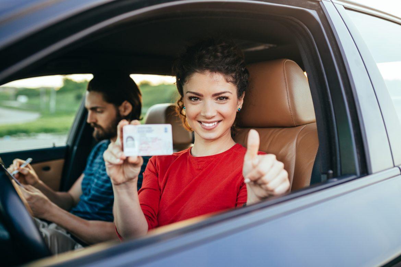 Badania na prawo jazdy - co musisz o nich wiedzieć? Uśmiechnięta kobieta w czerwonej bluzce siedzi w samochodzie po egzaminie i trzyma w dłoni nowe prawo jazdy.
