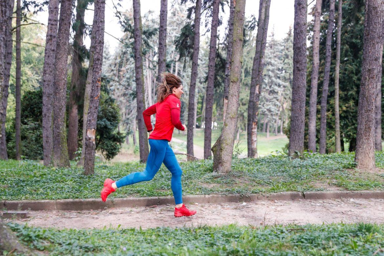 Bieganie dla początkujących. Jak zacząć biegać? Beata Sadowska w czerwonej bluzie i butach oraz niebieskich legginsach biega po parku.