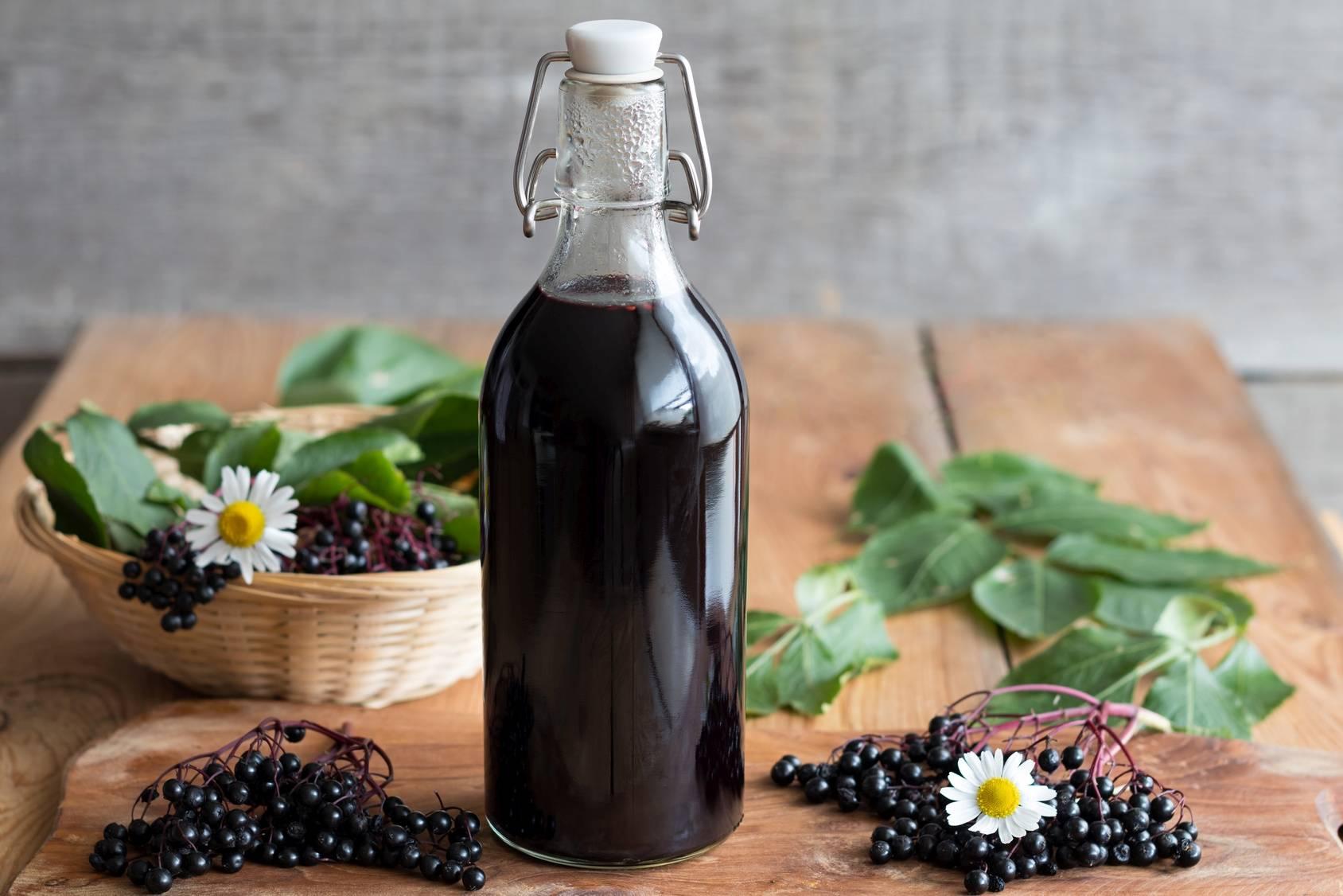 Sok z czarnego bzu. Na drewnianym stole stoi butelka soku z owoców czarnego bzu. Obok leżą gałązki z owocami bzu i pojedyncze liście. W tle stoi koszyczek.