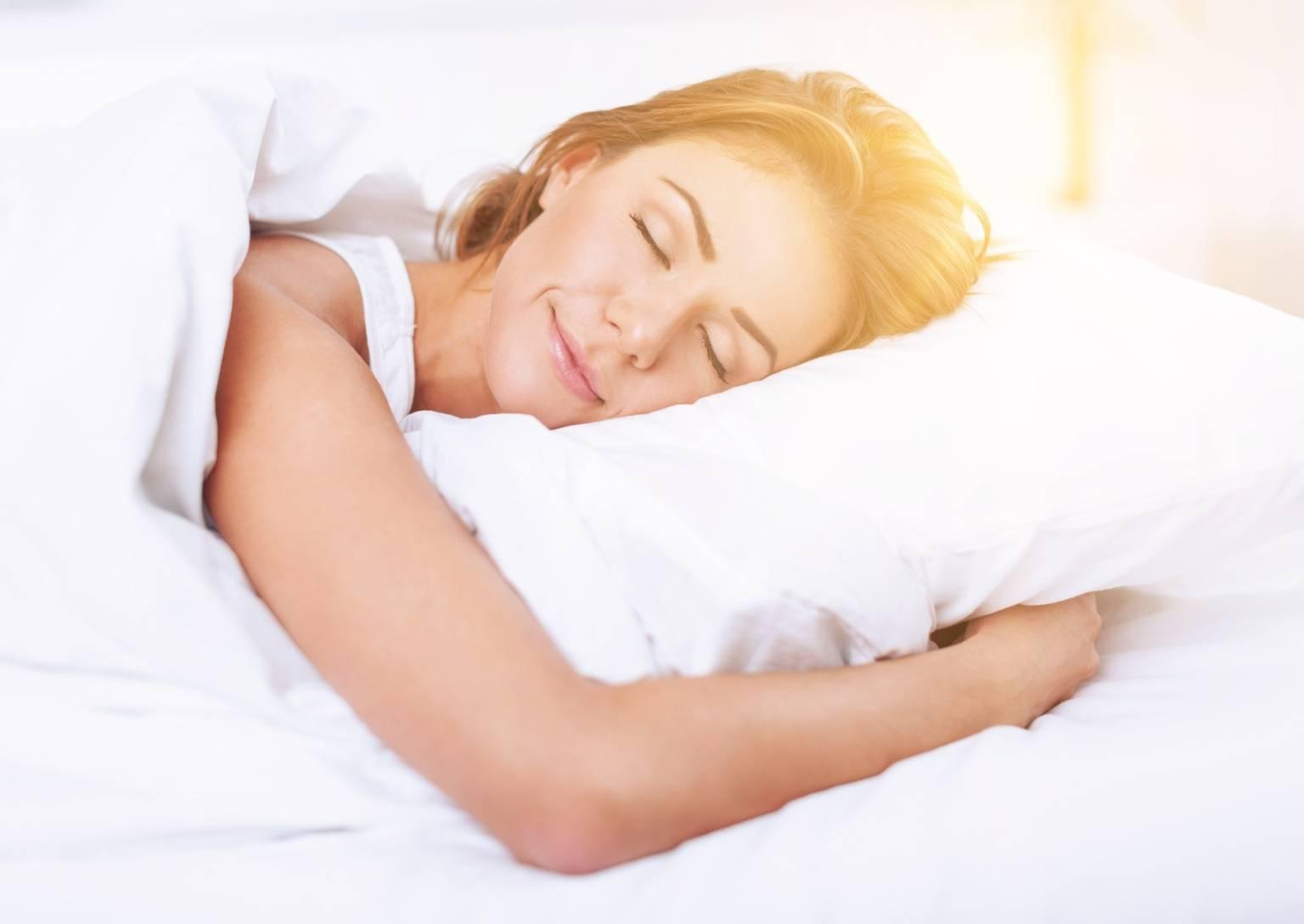 Naturalne sposoby na bezsenność. Kobieta spokojnie śpiąca w łóżku.
