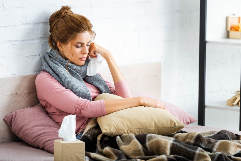 Jakie błędy popełniamy najczęściej podczas leczenia w domu? Hamujemy objawy choroby, które nas niepokoją, a tymczasem są one reakcją obronną naszego organizmu na drobnoustroje. Chora kobieta leż w łóżku z chusteczką w ręku.