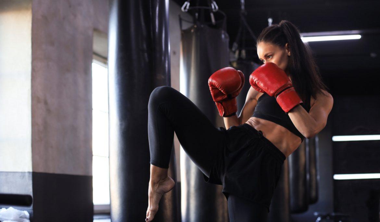Boks dla kobiet - czy boks może być kobiecy? Dziewczyna w czarnym stroju sportowym i czerwonych rękawicach ćwiczy kopnięcia na sali treningowej.