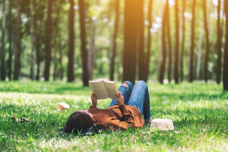 Borelioza - objawy, przyczyny, leczenie. Jak zdiagnozować boreliozę? Młoda kobieta czyta książkę na trawie w lesie.