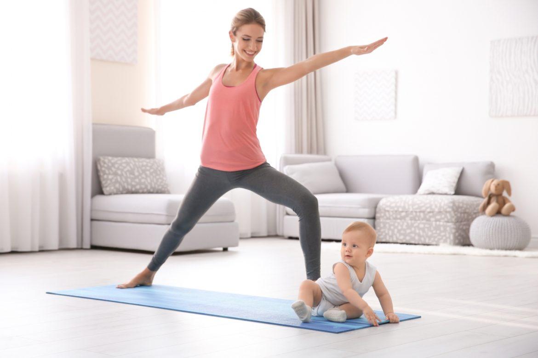 Brzuch po porodzie - jak zrzucić brzuch po ciąży? Młoda mama ćwiczy jogę z niemowlakiem na macie w domu.