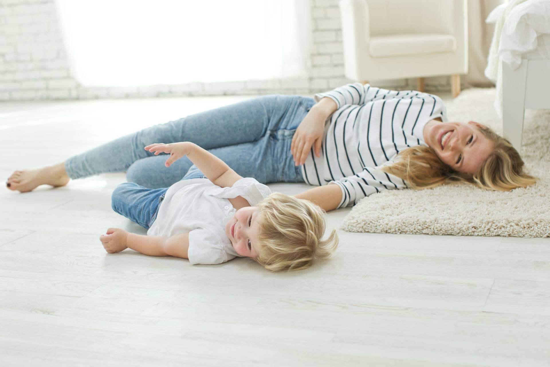 Bunt dwulatka - jak sobie z nim radzić? Mama bawi się na podłodze z synkiem.