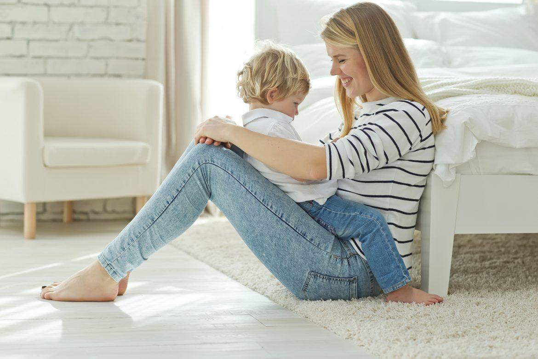 Jak radzić sobie z buntem dwulatka? Mama trzyma naburmuszonego synka na kolanach.