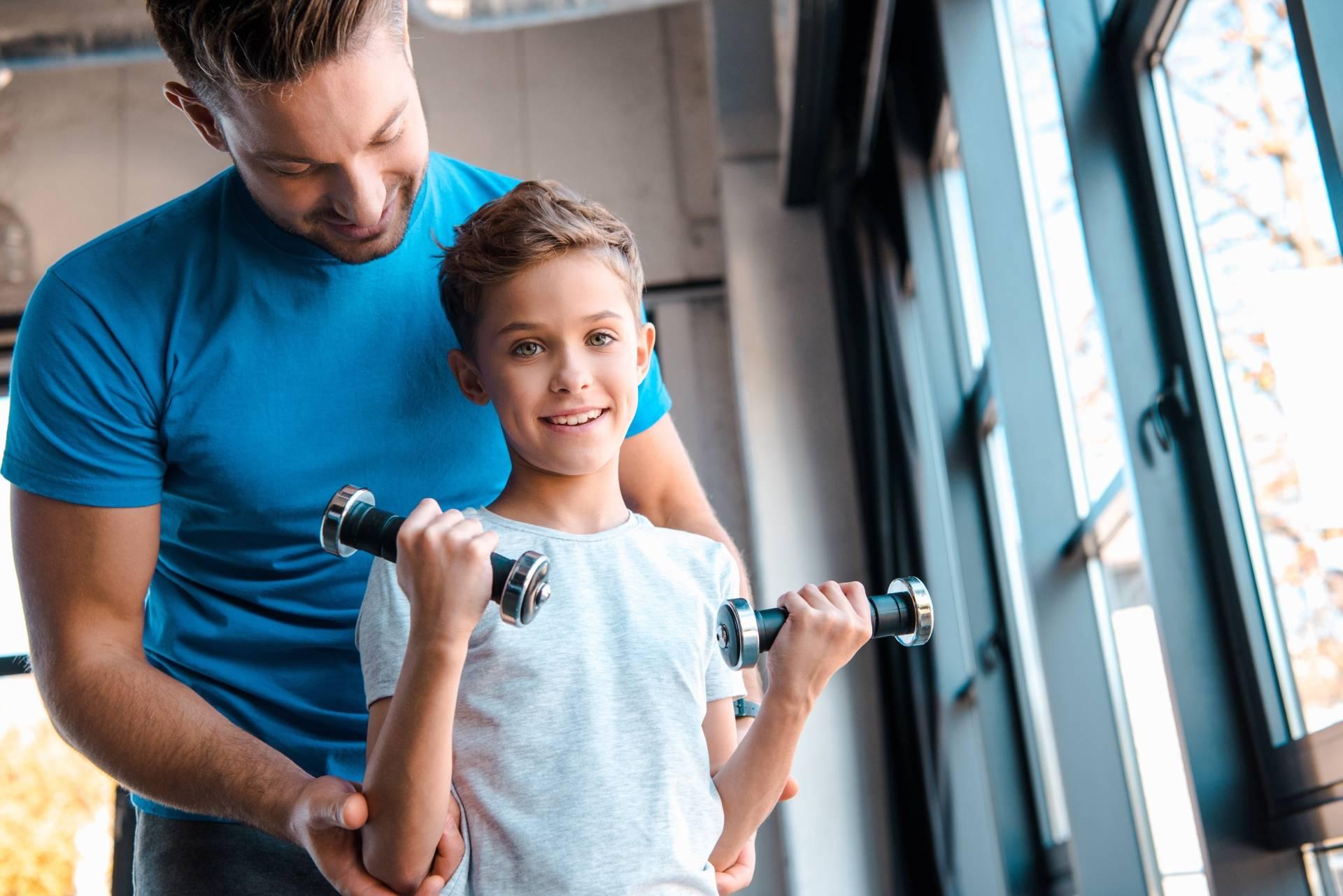 Siłownia dla dzieci. Ojciec pokazuje synowi jak trenować z hantlami.