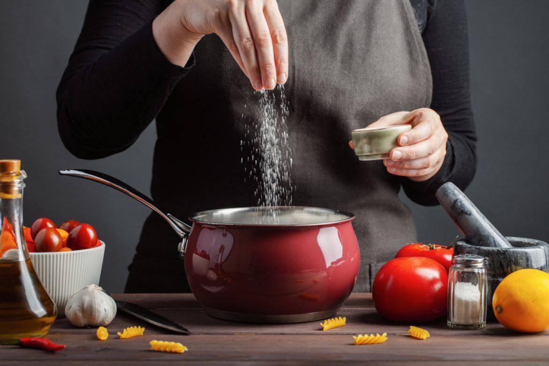 Chlor - jaką pełni rolę w organizmie? Gdzie szukać chlorków w pożywieniu? Kobieta soli zupę w garnku w kuchni.