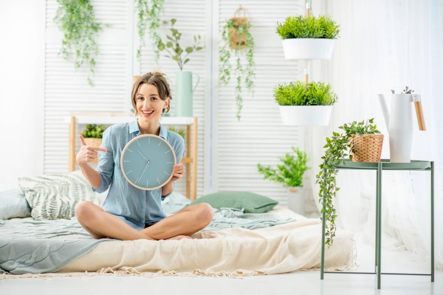 Chronobiologia - na czym polega życie we własnym rytmie? Czym są chronotypy i rytm dobowy? Kobieta siedzi na łóżku w sypialni, otoczona roślinami i trzyma w ręku zegar ścienny.