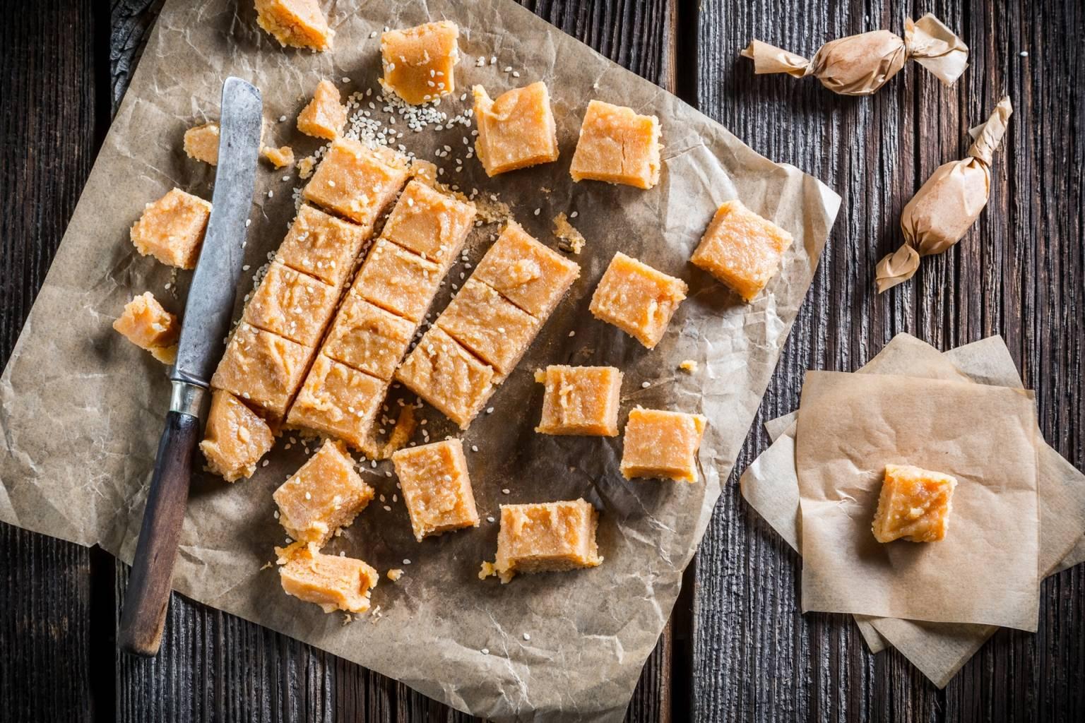 Jak leczyć cukrzycę typu 2? Na ciemnym drewnianym blacie, na papierze do pieczenia leżą pokrojone w kostkę domowe karmelowe cukierki. Obok leży długi nóż z drewnianą rękojeścią.