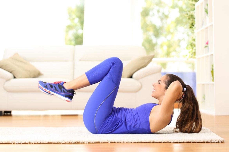 Ćwiczenia na kręgosłup lędźwiowy i brzuch. Młoda kobieta w niebieskim stroju sportowym ćwiczy w domu na macie.