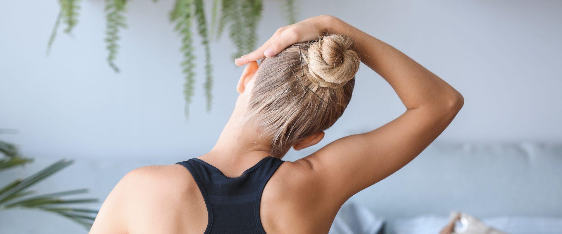 Ćwiczenia na kręgosłup szyjny. Kobieta w czarnym topie z włosami związanymi w kok siedzi zwrócona tyłem do aparatu i rozciąga szyję.