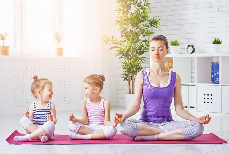 Ćwiczenia relaksacyjne dla dzieci - jak wygląda relaksacja dla dzieci? Mama z dwiema córeczkami medytuje na macie w domu.