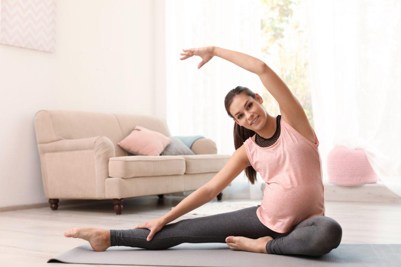 Ćwiczenia w ciąży - czy są bezpieczne? Kobieta w ciąży ćwiczy na macie w salonie.