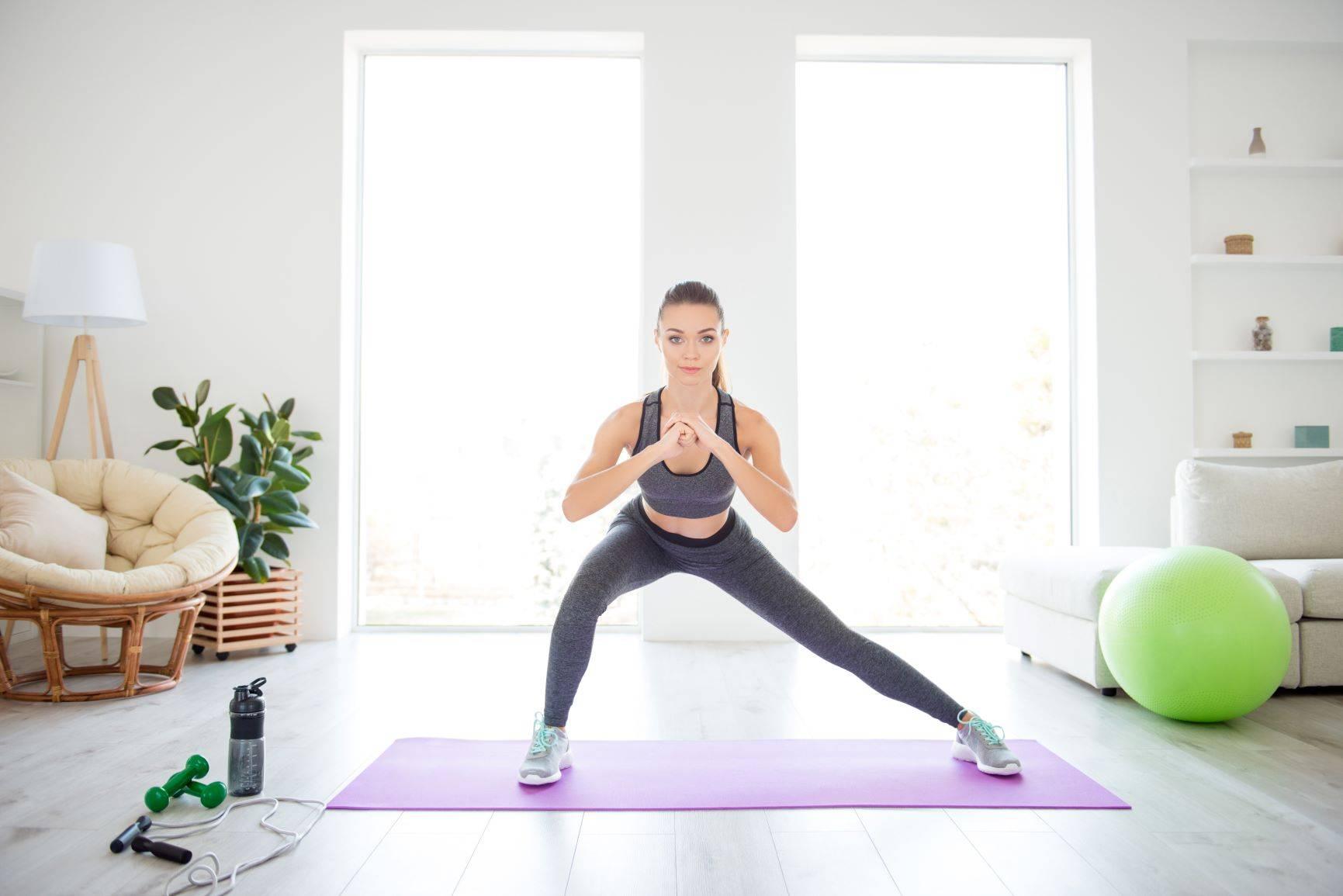 Tabata - szybkie, intensywne ćwiczenia w domu. Kobieta ćwiczy na macie w salonie.