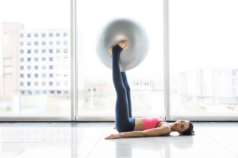 Jak ćwiczyć mięśnie Kegla (mięśnie dna miednicy)? Młoda kobieta w stroju sportowym ćwiczy - podnosi stopami piłkę do ćwiczeń.