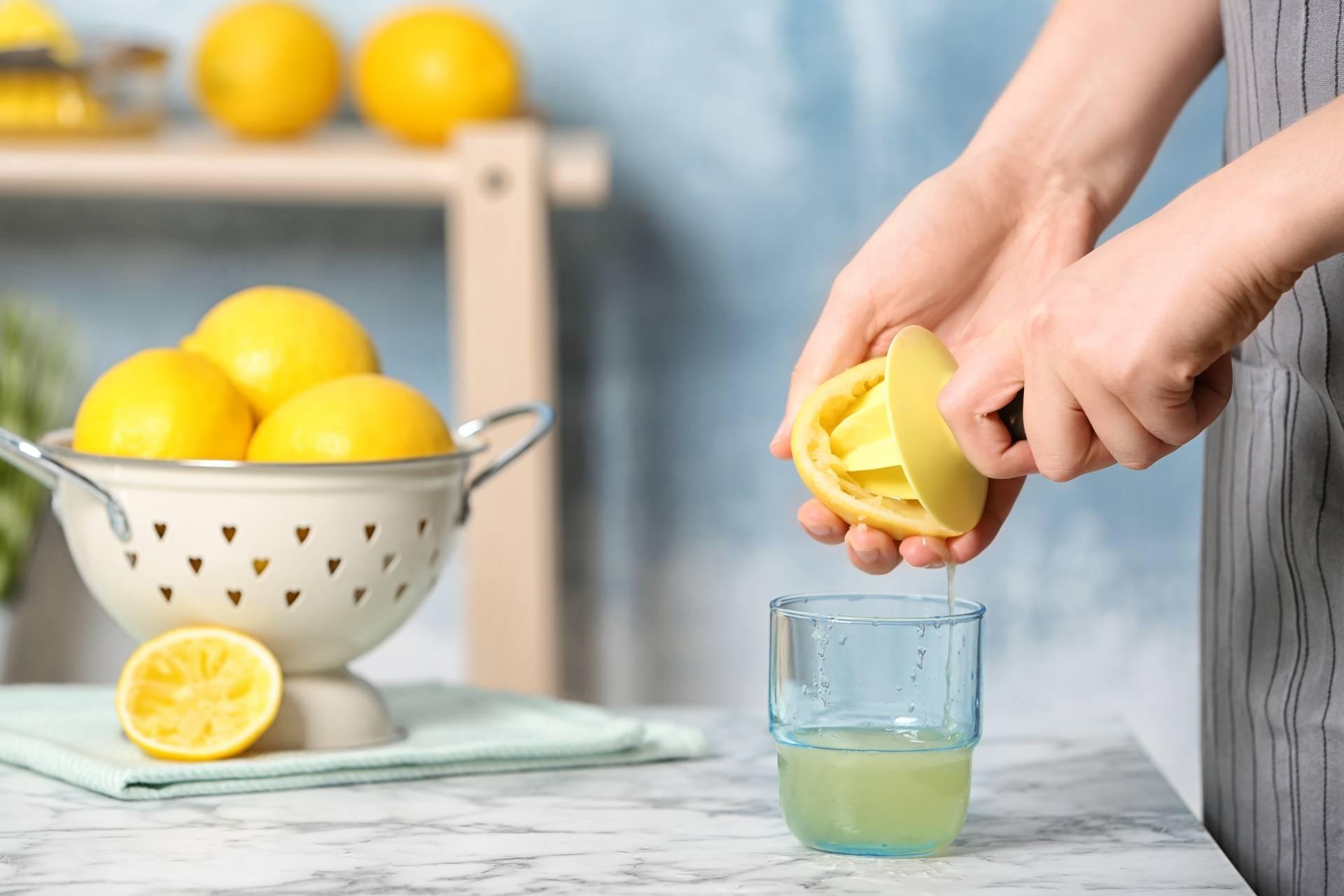 Cytryna na włosy. Kobieta wyciska sok z cytryny do szklanki. W tle leży durszlak z cytrynami i stoi szafka drewniana z pomarańczami.