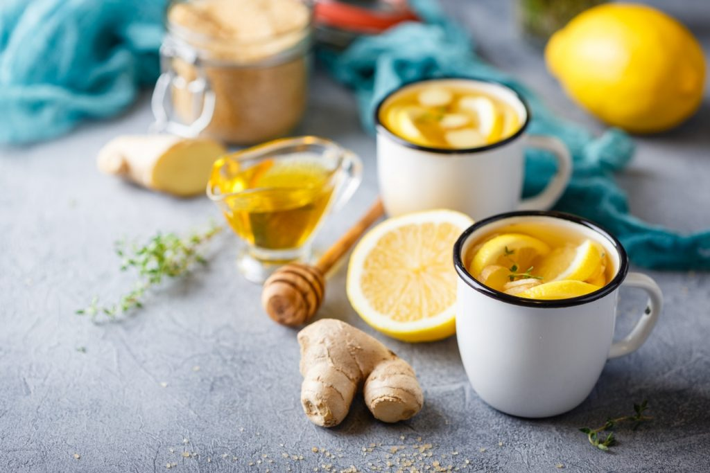 Dieta na odporność. Dwa białe kubki z herbatą z cytryną stoją na blacie, obok leży imbir, miód, cytryna.