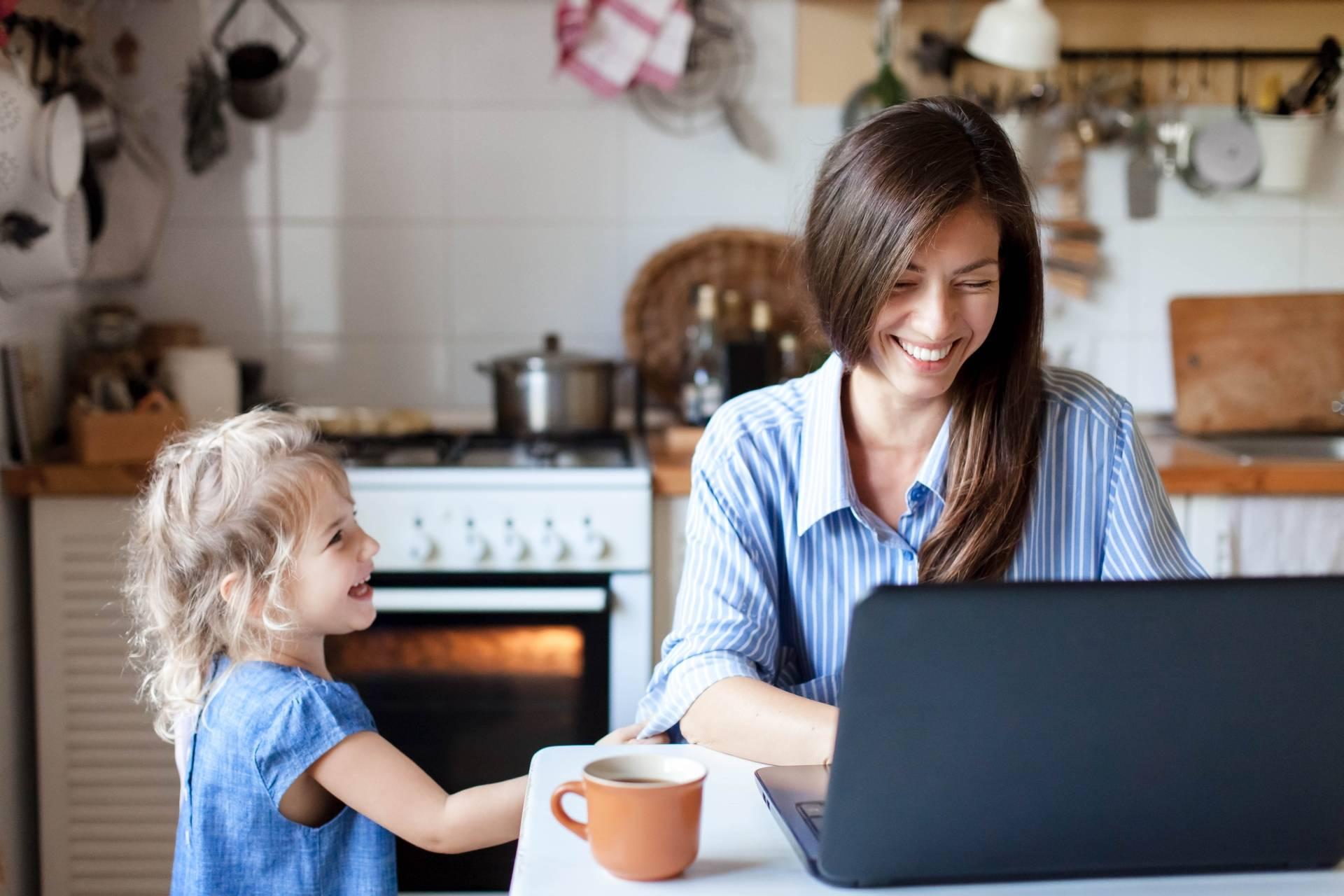 Work-life balance w dobie home office. Mama pracuje na laptopie w kuchni, obok stoi kilkuletnia córeczka i zachęca ją do zabawy.