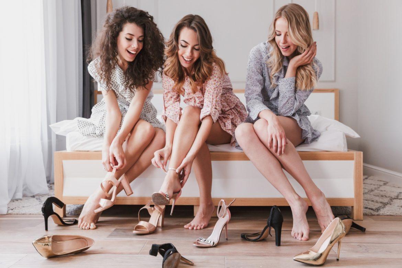 Dobry zwyczaj, nie pożyczaj - czego nie pożyczać innym? Jakie rzeczy codziennego użytku powinny być zarezerwowane tylko dla nas? Trzy przyjaciółki siedzą na łóżku w sypialni i przymierzają buty.