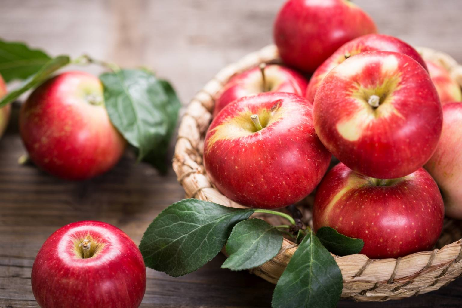 Przepis na ocet jabłkowy - jak zrobić go w domu? Czerwone jabłka w wiklinowym koszyczku.