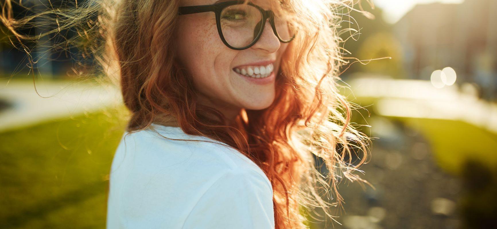 Czy optymizmu można się nauczyć? Uśmiechnięta rudowłosa dziewczyna w okularach z czarnymi rogowymi oprawkami uśmiecha się do obiektywu.
