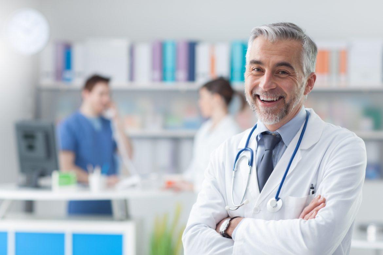 Czy przysłowia o zdrowiu są prawdziwe? Portret uśmiechniętego lekarza w gabinecie lekarskim.