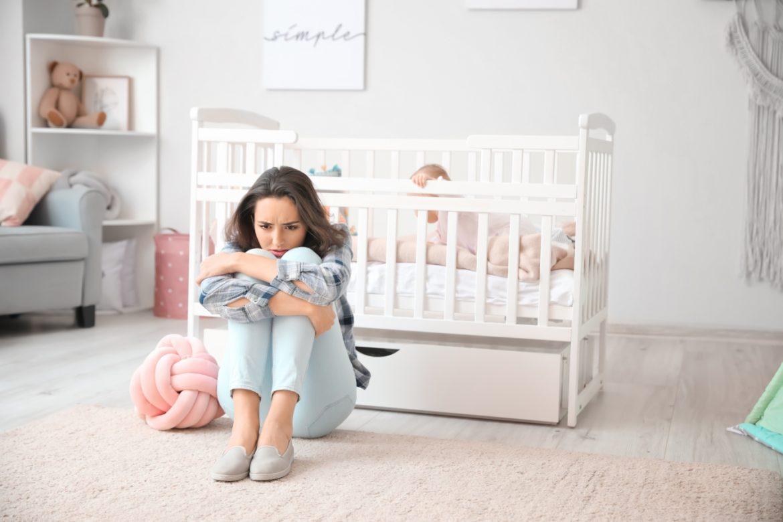 Depresja poporodowa - objawy i leczenie. Jak skutecznie wyleczyć depresję po porodzie? Smutna kobieta siedzi z podkulonymi nogami na środku dziecięcego pokoju, za nią stoi łóżeczko, w którym siedzi niemowlę.